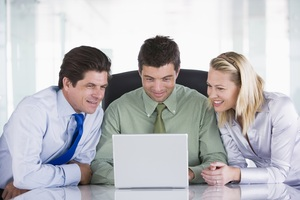 Three-businesspeople-in-office-with-laptop-smiling_ht2qd6phs